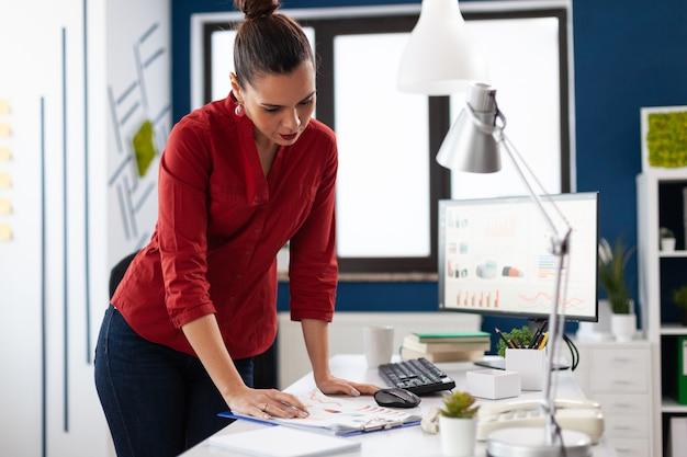 Stehende geschäftsfrau im büro des unternehmens, die offizielles dokument liest reading