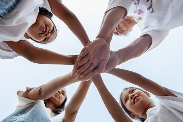 Stehende hände der asiatischen familie unterstützen zusammen. die familiengeneration zeigt gemeinsam einheit und teamwork.
