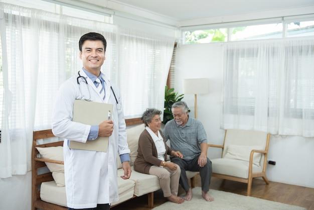 Stehende hand des jungen hübschen kaukasischen männlichen arztes, der dokumentdatei mit lächeln und zwei ältere alte asiatische ältere paare hält, sitzt auf couch, gesundheitswesen und medizinischem konzept.