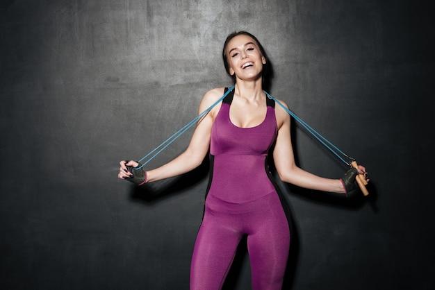 Stehende junge dame des glücklichen sports, die springseil hält.