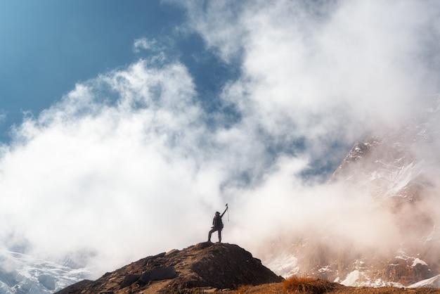 Stehende junge frau mit erhobenen armen auf dem berggipfel gegen blauen himmel mit niedrigen wolken am hellen tag