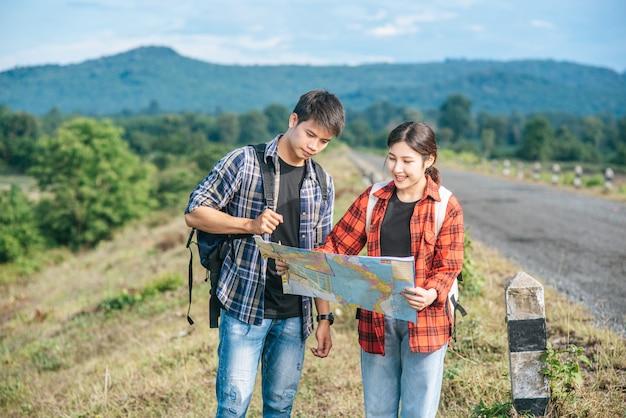 Stehende männliche und weibliche touristen betrachten die straßenkarte.