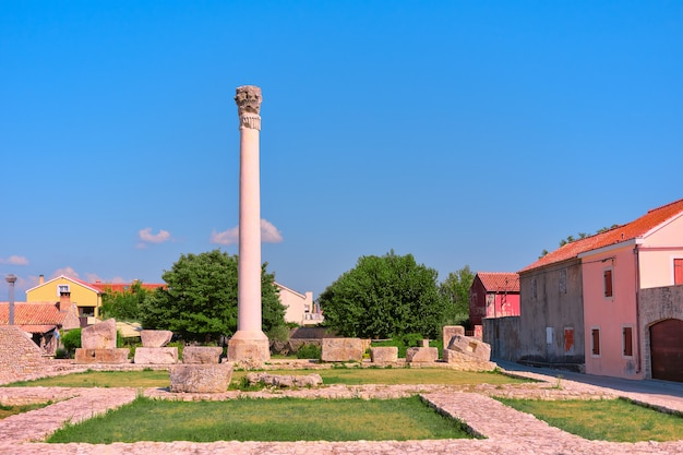 Stehende säule und ruinen des antiken römischen tempels in der historischen stadt nin in kroatien an einem hellen tag.