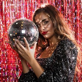 Stehende seitenansicht der frau, die eine discokugel anhält