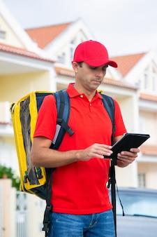 Stehende und lesende adresse des kaukasischen kuriers in tablette. fokussierter zusteller, der expressbestellung im gelben thermorucksack liefert.