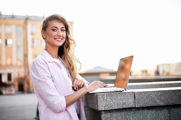 Stehender firmengebäude-sommertag der geschäftsfrau unter verwendung des laptop-geschäftsperson, der fern arbeitet. draussen
