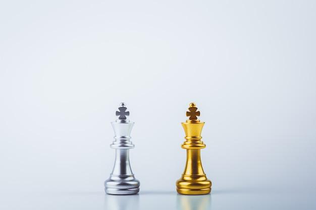 Stehender goldener königsschach trifft auf silberne königsfeinde.