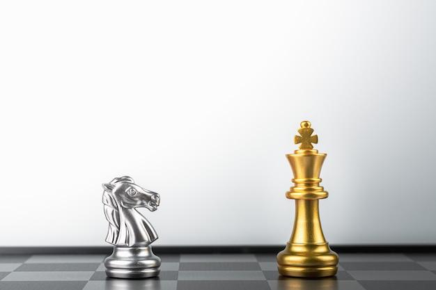 Stehender goldener königsschach trifft auf silberne ritterfeinde.