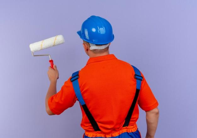 Stehender junger männlicher baumeister, der uniform und sicherheitshelm hält, der farbroller auf lila hält