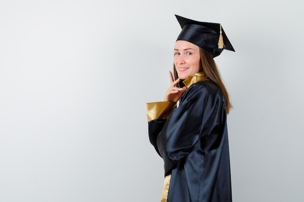 Stehender junger weiblicher absolvent beim aufstellen in der akademischen kleidung isoliert