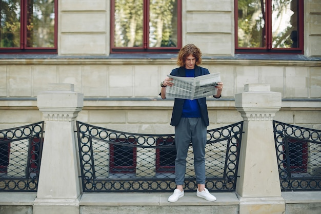 Stehender mann, der zeitung nahe altem artgebäude liest