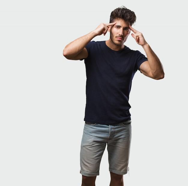 Stehender mann des jungen gutaussehenden mannes, der eine konzentrationsgeste macht