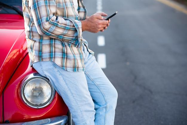 Stehender, nicht wiedererkennbarer mann, der telefon im freien benutzt, nicht erkennbare menschen mit handy-chat oder sms mit dem modernen lebensstil des autos mit überall roaming-verbindung chat
