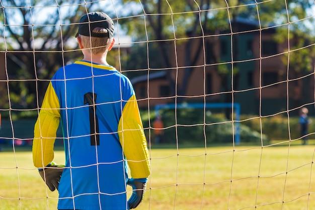 Stehender schutz des jungen torhüterjungen vor seinem teamziel während eines spiels