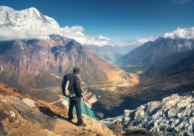 Stehender sportlicher mann mit rucksack auf dem berggipfel und blick auf schönes gebirgstal bei sonnenuntergang