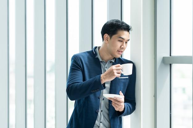 Stehender und trinkender kaffee des intelligenten asiatischen geschäftsmannes morgens nahe dem fenster im büro des hohen gebäudes. portrait des durchdachten geschäftsmannes mit exemplarplatz. geschäftsleute konzept.