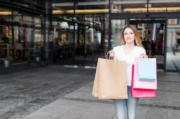 Stehendes äußeres mall der jungen frau nach dem einkauf