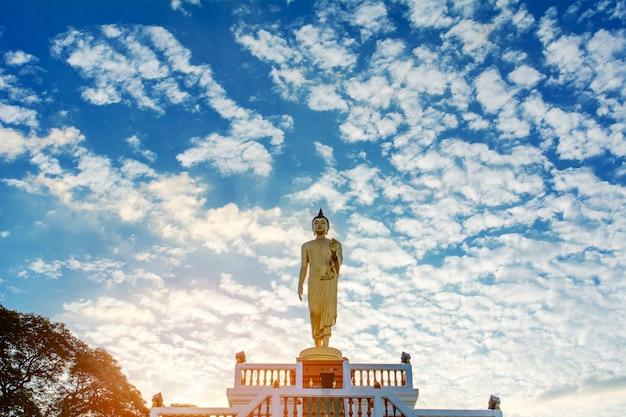 Stehendes buddha-bild und der blaue himmel, religiöse konzepte
