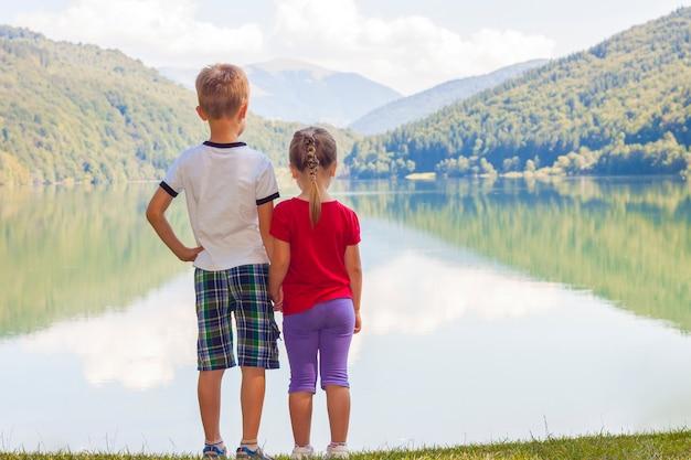 Stehendes händchenhalten des kleinen jungen und des mädchens auf der bank von einem see
