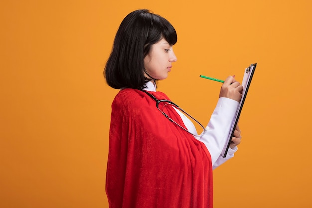 Stehendes in der profilansicht junges superheldenmädchen, das stethoskop mit medizinischer robe und umhang trägt, die etwas auf zwischenablage schreiben