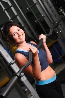 Stehendes lächelndes kaukasisches weißes brünettes mädchen, das langhantel mit gewicht in händen hält. körperliche bewegung im fitnessstudio.