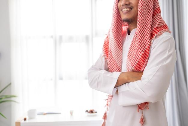 Stehendes porträt des arabischen muslimischen geschäftsmannes verschränkte seinen arm gegen das fenster