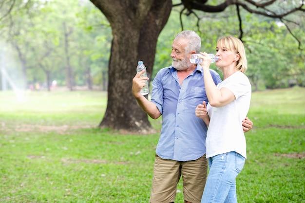 Stehendes trinkwasser des älteren paares des portraits am park