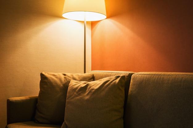 Stehlampe neben dem sofa im zimmer oder hotelzimmer