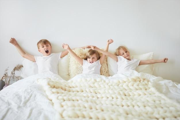 Steige auf und scheine. isolierte horizontale aufnahme von drei kleinen geschwistern und ihren zwei älteren brüdern, die identische weiße t-shirts tragen, auf dem bett sitzen, die arme ausstrecken und am morgen gähnen