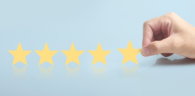 Steigen sie auf, indem sie fünf sterne in der menschlichen hand erhöhen, das klassifizierungskonzept für die bewertungsbewertung erhöhen