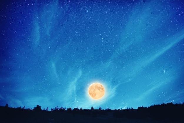 Steigen sie bei vollmond nachts am dunkelblauen himmel mit vielen sternen und wolken auf Premium Fotos