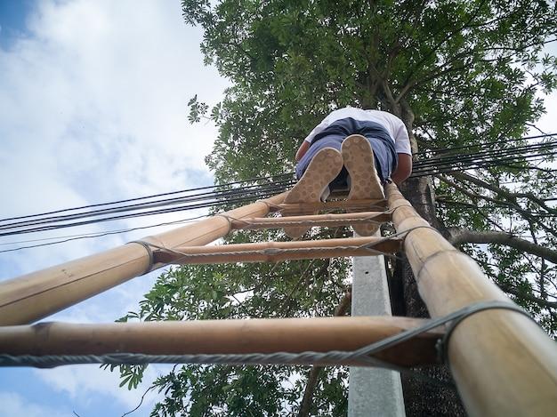 Steigender leitermann auf einem bambustreppenhaus bei der arbeit