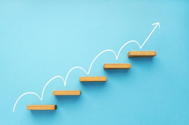 Steigender pfeil auf der treppe auf blauem hintergrund. wachstum, geschäftswachstum, erfolgskonzept. platz kopieren