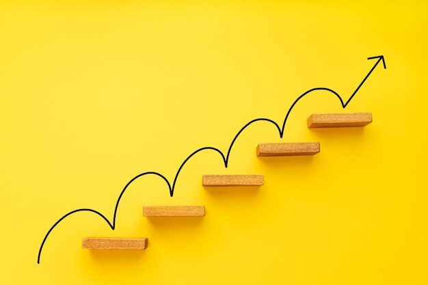Steigender pfeil auf der treppe auf gelbem hintergrund. wachstum, geschäftswachstum, erfolgskonzept. platz kopieren