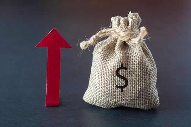 Steigern oder steigern sie ihr einkommen mit einem richtungspfeil, geld und einer tasche über der dunkelheit. finanziell. copyspace.