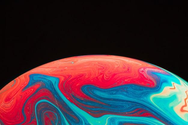 Steigung geplätscherte mehrfarbige seifenblase auf schwarzem hintergrund