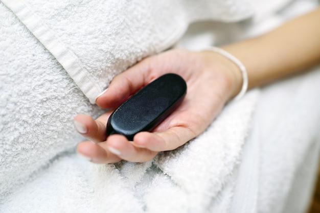Stein für steintherapie nahaufnahme in der hand einer frau. spa, entspannen, massieren