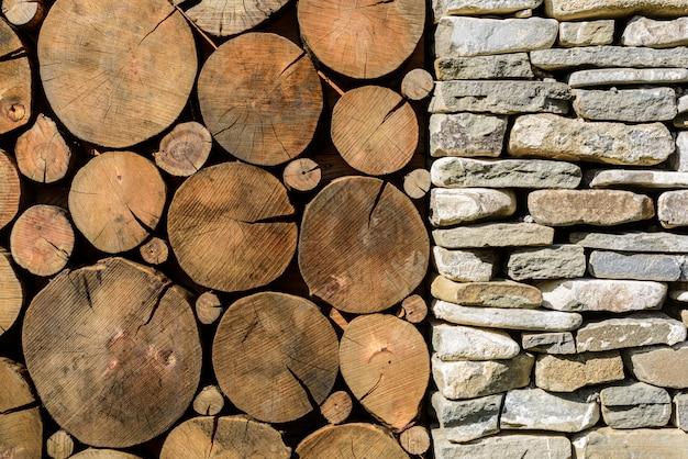 Stein und holz hintergrund. gebäude mit steinsäulen- und holzquerschnittbeschaffenheit.