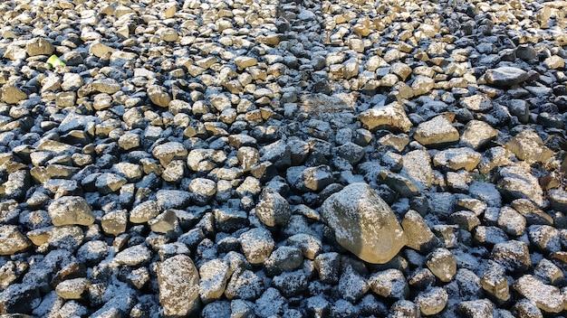 Steinbedeckter boden mit einer dünnen schneeschicht im winter