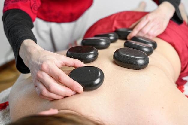 Steinbehandlung. junge frau, die vorne liegt und eine massage am spa mit heißen steinen auf ihrem rücken genießt. schönheitsbehandlungskonzept.