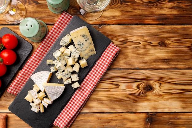Steinbrett mit geschnittenem käse auf holztisch schließen oben