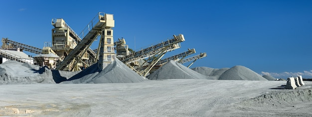 Steinbruchmaschinen und kieshaufen über blauem himmel steinzerkleinerungs- und siebanlagenpanorama