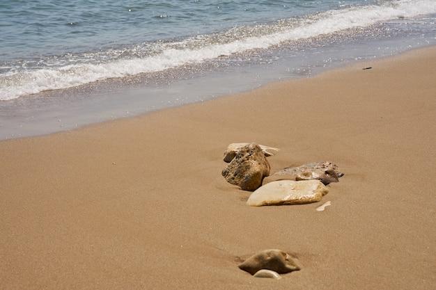 Steine am tropischen sandstrand mit verschwommenen wellen im hintergrund.
