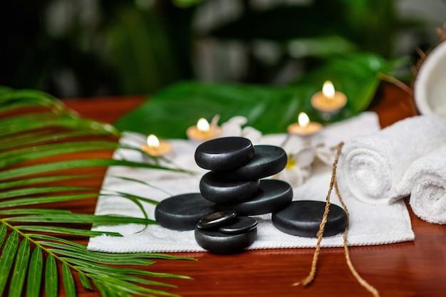 Steine für einen therapiestein auf einem frottiertuch, daneben kerzen und ein blumenzweig