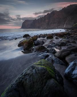 Steine im strand unter dem bewölkten himmel bei sonnenuntergang