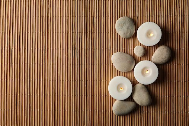Steine und kerzen auf bambushintergrund. zen-konzept