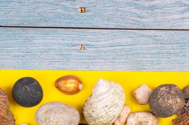Steine und muscheln auf blauem holzhintergrund und gelbem hintergrund.marinethema