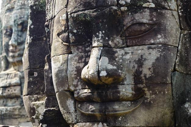 Steingesichter in bayon, angkor thom tempel, sonnenunterganglicht des selektiven fokus. buddhismusmeditationskonzept, weltberühmtes reiseziel, kambodscha-tourismus.