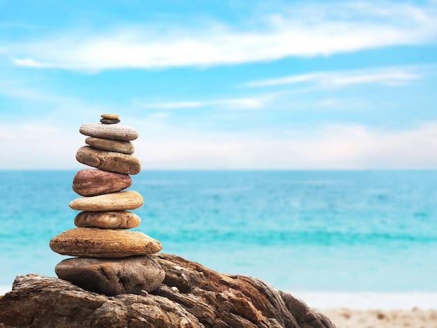Steinhaufen als pyramide auf sommerstrandhintergrund