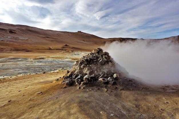 Steinhaufen bei hverir in island mit schwefelquellen, fumarolen und schlamm als geothermische aktivität.